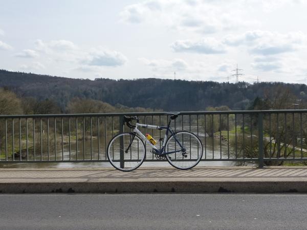 Rennrad an einem Brückengeländer